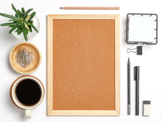 Workspace home office white background with cork board, coffee, clips and accessories. Top view with copy space, flat lay.