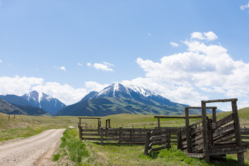 An old wooden corral in Paradise Valley Montana next to a gravel road that leads to the rugged, snow capped mountains in the distance. Fluffy white clouds above.