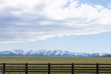 Wooden fence and prairie in the foreground with rugged snow capped mountains in the background. Fluffy gray and white clouds against light blue sky are above.