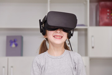 Young little girl wearing virtual reality device. Headset. Glasses with virtual screen.