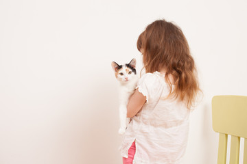 A child playing with a white kitten