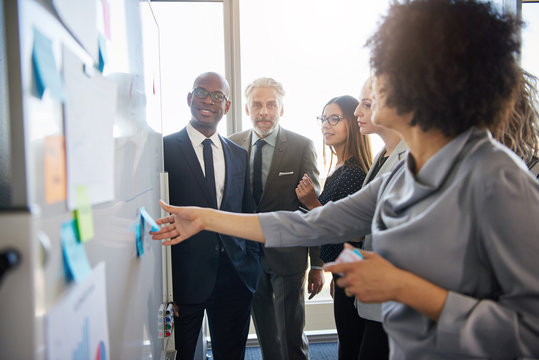 Group of mixed business people having a meeting using a white board