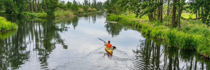 Panorama of a girl kayaking on a river, beautiful nature landscape