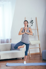 Young cheerful attractive woman practicing yoga