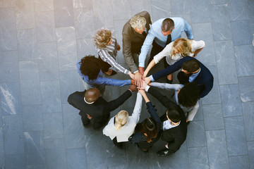 Multiracial office workers having teambuilding with hands stacked