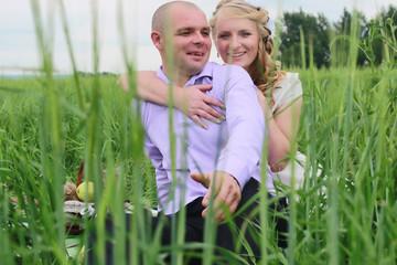 Couple lovers walking in field in summer day
