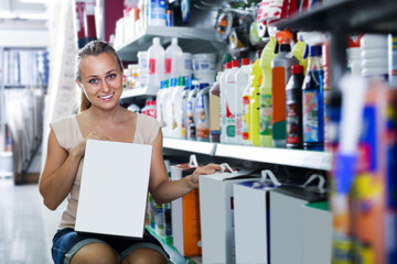 Smiling woman customer holding box with dry filler in hypermarket