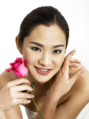 Beautiful lady with pink rose on one cheek and a hand on the other