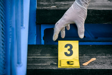 Crime scene investigation, putting the crime scene marker on wood stairs