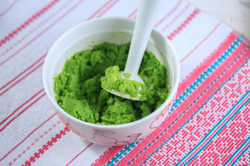 Broccoli puree in a white plate on a light background