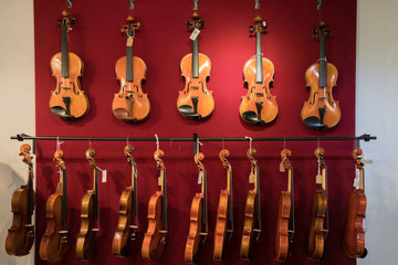 Spoed Foto op Canvas Muziekwinkel Violins are hanging on the red wall in the shop.