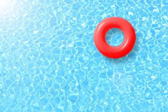 red swimming pool ring float in blue water and sun bright. concept color summer.