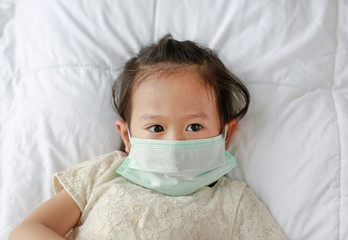 Little girl wearing a protective mask lying on the bed.