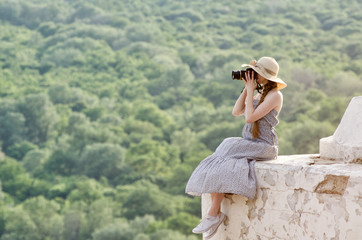Girl sits on a hill and takes pictures against a forest