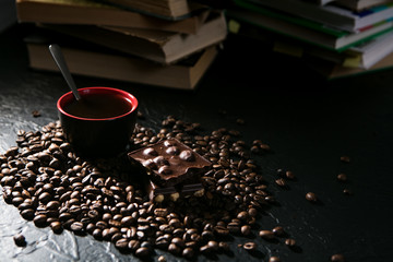Wall Murals Coffee beans coffee cup and coffee beans and chocolate on the background of books