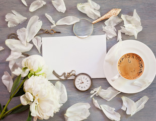 Flat lay of empty card, coffee cup,  old pocket watch and flowers with copy space. Top veiw