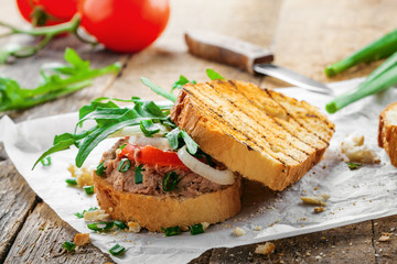 Classic tuna salad sandwich with tomato, onion and arugula on a table. Delicious healthy meal made of fish, vegetables and toasts.