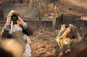 A young couple of photographers a man and a woman taking pictures in the countryside