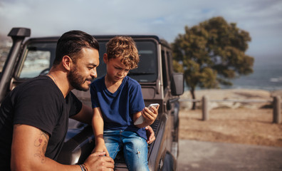 Father and son in front of car using smart phone