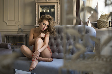 picture of lovely blonde in lingerie sitting on the sofa