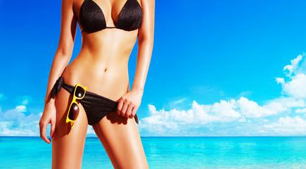 Beautiful woman body with black bikini standing on the beach. Yellow sunglasses. Perfect shining skin.