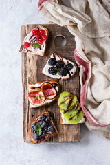 Variety of dessert sandwiches with berries and cream cheese and chocolate swirl. Red currant, blueberries, sliced kiwi, figs on serving board over white texture background. Flat lay, summer appetizer