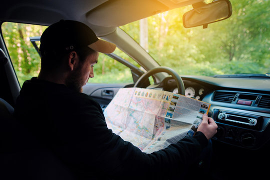 Losted in the forest young driver sitting in car while holding map and looking aside