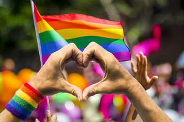 Hands making heart sign in front of rainbow flag