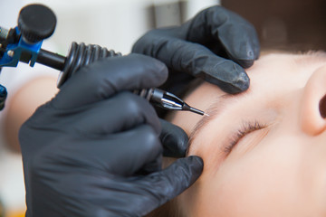 Cosmetologist applying permanent makeup on brows