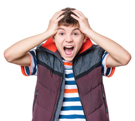 Emotional portrait of caucasian teen boy. Amazed teenager screaming looking at camera. Handsome surprised child, isolated on white background.