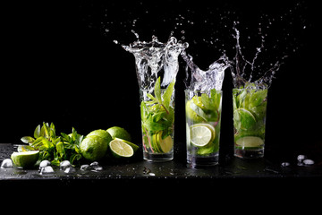 Mojito summer beach refreshing tropical cocktail splash in glass highball alcohol drink with soda water, lime juice, mint leaves, sugar, ice and rum