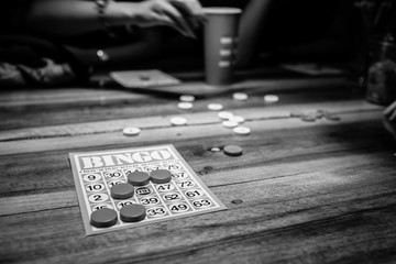 Black and white photo of people playing bingo game and having very much fun of bingo game playing on a wooden table. Bingo card on the wooden table and the  game of chance is played.