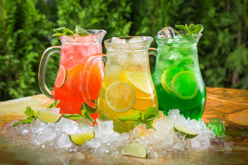 Summer cocktails in jugs in the ice with lime and mint, sangria