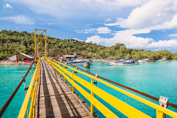 Tropical island in Indonesia, ocean and yellow bridge.