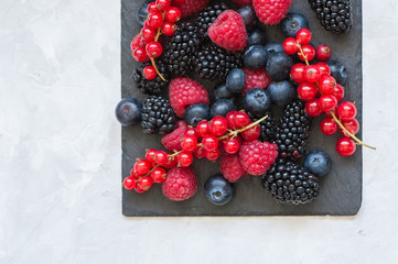 of berries raspberries red currants blueberries and blackberries on black slate board. White stone background.  Overhead view and copy space
