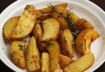 Close up Gourmet Spicy Fried Potato Wedges on Plate with Herb on Top. Isolated on White Background.