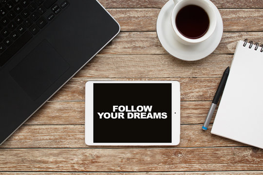 Tablet on desktop with follow your dreams text.