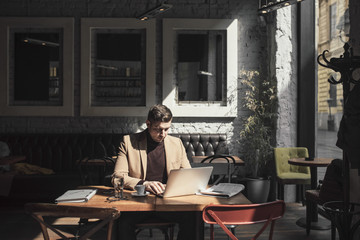 Handsome Caucasian businessman sitting at cafe  and working on laptop.