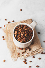 Conceptual Breakfast, Cup with coffee beans on a white concrete background.
