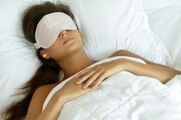 Woman is wearing eye mask and using earplugs