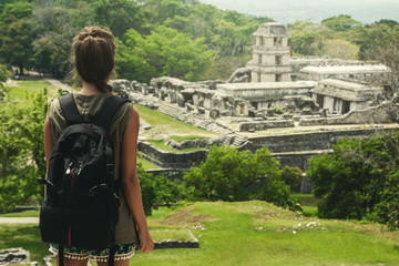 Woman with backpack beside ancient Mayan ruins