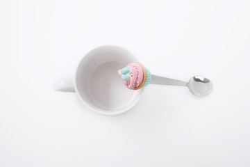 White cup with a spoon and cookies on a white background