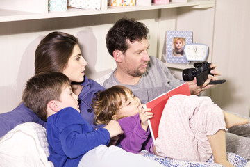 Family in bed taking selfie with camera