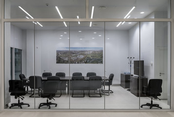 A modern meeting room with transparent partitions, with a large table and comfortable office chairs. Fototapete