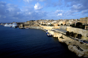 Cruise ship and traditional stone made buildings in city Valletta,Malta with coastline and blue sky in background