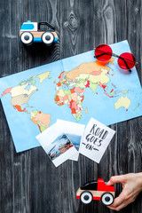 children tourism outfit with map and pictures on dark background flat lay