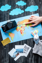 tourist equipment with map and photos for traveling with kids on dark background top view mock up