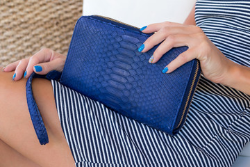 Luxury snakeskin wallet purse in woman hands. Bali island, handmade purse, fashion.