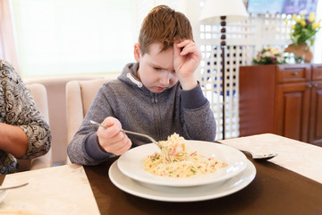 Preteen handsome boy with a plate of pasta refuse to eat