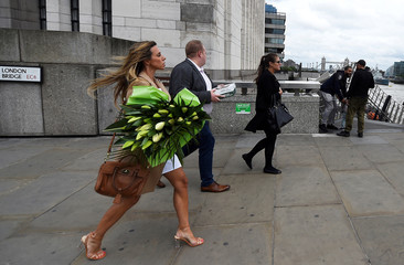 A woman carries a bunch of flowers across London Bridge, in London